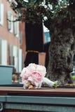 Lyxig brud- bukett av vita pioner och rosor på bänken Arkivfoton