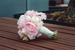 Lyxig brud- bukett av vita pioner och rosor på bänken Royaltyfria Foton