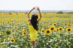 Lyxig brunett i en gul klänning med blommor Royaltyfri Fotografi