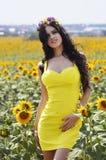 Lyxig brunett i en gul klänning med blommor Arkivbild