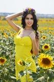 Lyxig brunett i en gul klänning med blommor Fotografering för Bildbyråer