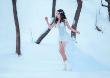 Lyxig brunett i en vit klänning royaltyfri foto