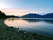 Lyxig fantasisolnedgång över den stilla sjön på tio e.m. arkivfoto