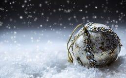 Lyxig jul klumpa ihop sig i snön och de snöig abstrakta platserna Julbollen blänker på bakgrund Arkivfoto