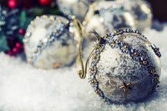Lyxig jul klumpa ihop sig i snön och de snöig abstrakta platserna Julbollen blänker på bakgrund Royaltyfria Foton