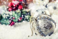 Lyxig jul klumpa ihop sig i snön och de snöig abstrakta platserna Julbollen blänker på bakgrund Royaltyfri Bild