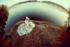 Lyxig kvinna i en skog i en lång tappningklänning nära sjön royaltyfri bild