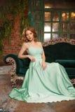 Lyxig kvinnamodell i enfärgad klänning som sitter på en tappningsoffa Skönhetflicka med en bedöva makeup och frisyr royaltyfria bilder