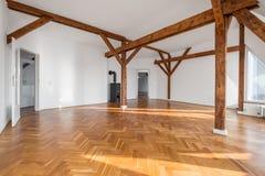 Lyxig lägenhet, tomt vindrum med spisen och träbea royaltyfri foto