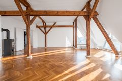 Lyxig lägenhet, tomt vindrum med spisen och träbea royaltyfri fotografi
