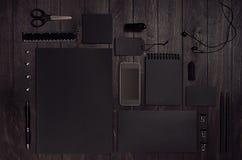Lyxig mall för företags identitet med den svarta tomma uppsättningen för pappers- brevpapper, telefon på mörkt elegant wood bräde royaltyfri foto