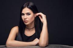 Lyxig modell för brunett i mörka klänning och smycken Arkivbild