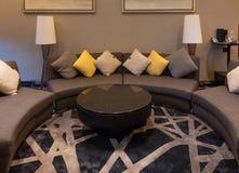 Lyxig modern vardagsrum med kuddar, möblemang, bildramen och soffagarnering på natten Bakgrund för hemmiljödesign royaltyfri bild