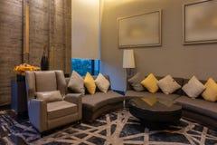 Lyxig modern vardagsrum med kuddar, möblemang, bildramen och soffagarnering på natten Bakgrund för hemmiljödesign royaltyfria foton