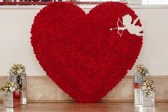 Lyxig röd hjärta av rosor och kupidonet med pilar på brölloprecep Fotografering för Bildbyråer