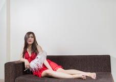 Lyxig rödhårig mankvinna i en röd klänning på den bruna soffan Arkivfoto
