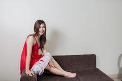 Lyxig rödhårig mankvinna i en röd klänning på den bruna soffan Arkivbilder