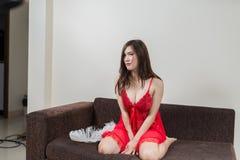 Lyxig rödhårig mankvinna i en röd klänning på den bruna soffan Royaltyfria Bilder