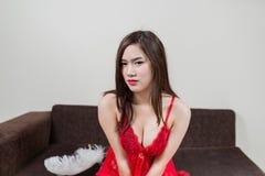 Lyxig rödhårig mankvinna i en röd klänning på den bruna soffan Royaltyfria Foton