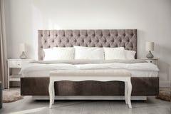 Lyxig säng i rum arkivbilder