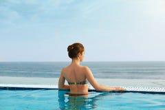 Lyxig semesterort Kvinna som kopplar av i o?ndlighetssimbass?ngvatten H?rlig lycklig sund kvinnlig modell Enjoying Summer Travel  royaltyfri foto