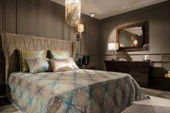 Lyxig sovruminre med sniden wood säng, skänk och på nätterna Arkivfoton