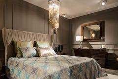 Lyxig sovruminre med sniden wood säng, skänk och på nätterna Royaltyfria Bilder