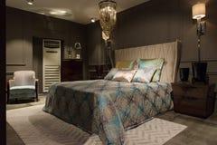Lyxig sovruminre med sniden wood säng, skänk och på nätterna Royaltyfri Bild