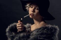 Lyxig stil för ung kvinna på grå väggrökare arkivfoto