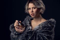 Lyxig stil för ung kvinna som isoleras på grå väggmakeup royaltyfri fotografi