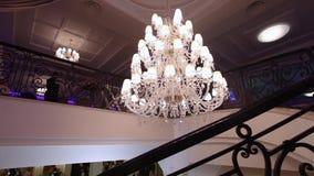 Lyxig stor kristallkrona som hänger i slotten Tappningbelysninglampor med ljusa kulor och många hängear lager videofilmer