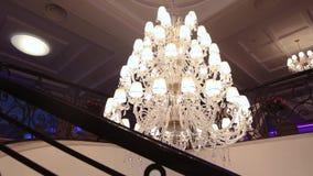 Lyxig stor kristallkrona som hänger i slotten Tappningbelysninglampor med ljusa kulor och många hängear arkivfilmer