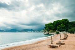 Lyxig strandsemesterort med sunbeds och paraplyer med regnig himmel Arkivbild