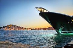 Lyxig Superyacht pilbåge på natten med den Eivissa staden Dalt Vila i Ibiza Spanien royaltyfri fotografi
