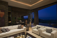 Lyxig vardagsrum i hus på natten Royaltyfria Bilder