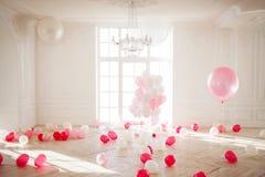 Lyxig vardagsrum med det stora fönstret till golvet Slotten fylls med rosa ballonger Fotografering för Bildbyråer