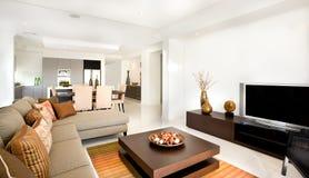 Lyxig vardagsrum med ett kök bredvid det i det modernt ho royaltyfria bilder