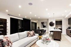 Lyxig vardagsrum med soffor och kuddar bredvid kök royaltyfria bilder