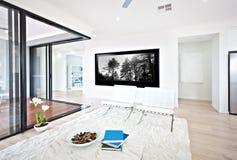 Lyxig vardagsrum- och exponeringsglasdörringång till insidan royaltyfri foto