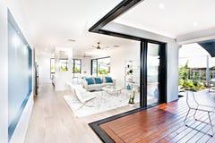 Lyxig vardagsrum och trähall bredvid en uteplats Royaltyfri Foto