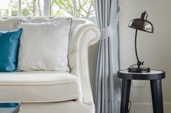 Lyxig vit soffa med lampan i vardagsrum Arkivbilder