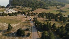 Lyxiga bilritter på bergvägen i solnedgång Filmiskt flyg- skott arkivfilmer