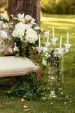 Lyxiga bröllopgarneringar med bänk-, stearinljus- och blommacompis Royaltyfri Fotografi