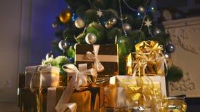Lyxiga gåvaaskar under julgranen, hemgarneringar för nytt år, guld- inpackning av jultomtengåvor, festligt granträd arkivfilmer