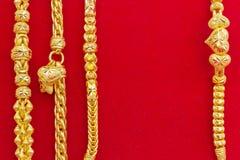 Lyxiga guld- armband på röd flanell Royaltyfri Bild