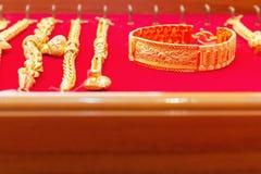 Lyxiga guld- armband på röd flanell Arkivfoton
