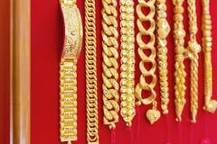 Lyxiga guld- armband på röd flanell Royaltyfria Foton