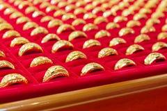 Lyxiga guld- cirklar på röd flanell Royaltyfri Foto