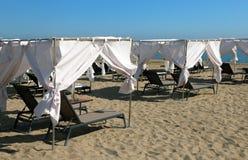 Lyxiga kabiner för att solbada med sunbeds på den sandiga stranden Royaltyfria Foton