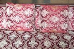 Lyxiga kuddar på säng Arkivbild